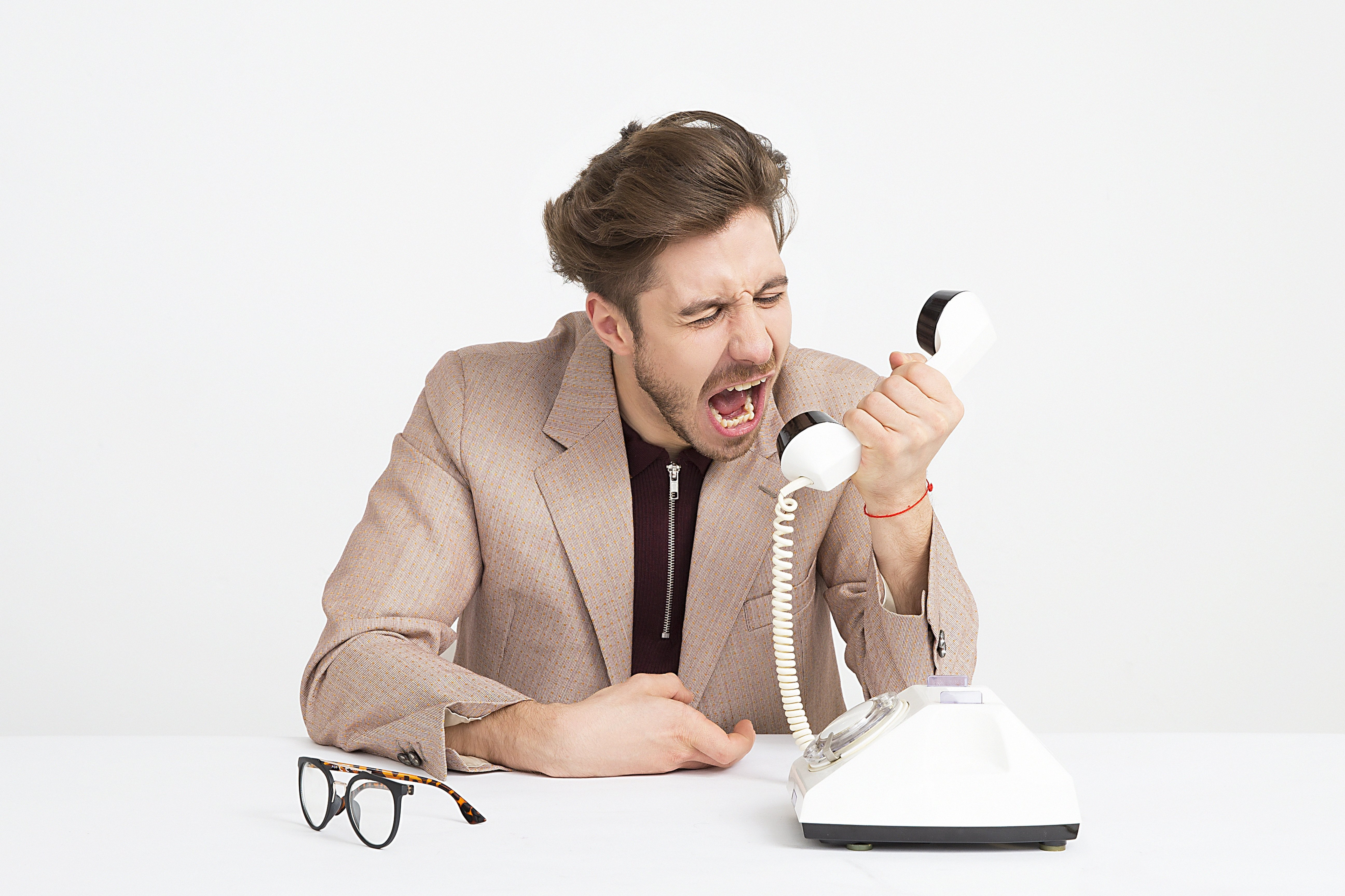 A man is upset by a surprise medical bill and is yelling at the phone